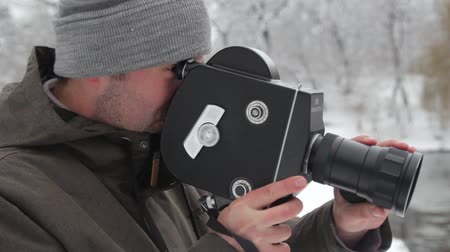 A male (man) cameraman shoots video on an old vintage camera Krasnogorsk in the park in winter. Kyiv. Ukraine