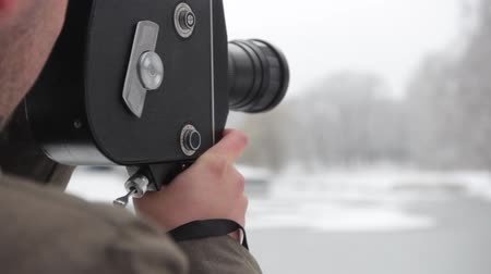 filmmaker : A male (man) cameraman shoots video on an old vintage camera Krasnogorsk in the park in winter. Kyiv. Ukraine