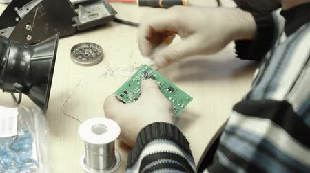 ellenállás : A worker is working on the creation of an electronic board. Close-up.