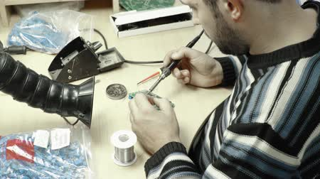 микрочип : A worker is working on the creation of an electronic board. Close-up.