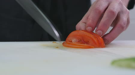 разделочная доска : Man in the kitchen cutting tomato
