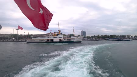 ferryboat : istanbul, Turkey - May 2018: istanbul ferry departing from Kadikoy pier into bosphorus with waving Turkish flag