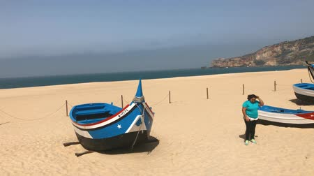 fishing village : Nazare, Portugal - April 2018: Colorful traditional old wooden fishing boat on the beach of fishing village of Nazare.The high cliff of Nazare Sitio and its lighthouse fortress on background.