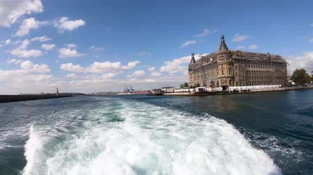 ferry terminal : istanbul, Turkey - October 2018: Haydarpasa railway station with a ferry sailing infront. The building is being restored after a roof fire Stock Footage
