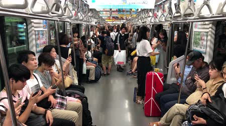 tokyo station : Tokyo, Japan - August 2018: People using smart phones inside subway wagon while riding. Concept of lack of communication in modern society.
