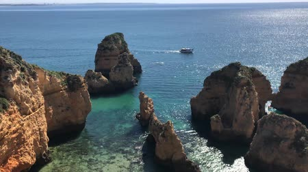 ponta da piedade : Lagos, Portugal - April 2018: Fishing boats on turquoise sea water at Ponta da Piedade, Algarve region, Portugal