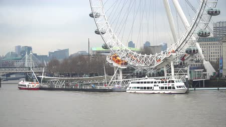 westminster : London, United Kingdom - January 2019: Boats and Thames River in Central London with London Eye Pier