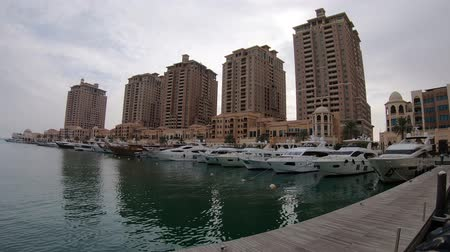 east pearl : Doha, Qatar - February 2019: Yachts and boats in the marina area inside residential area of The Pearl, close to Doha, an artificial island spanning nearly four million square meters.
