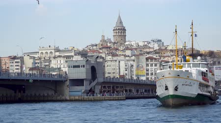 imparatorluk : istanbul, Turkey - March 2019: Galata Bridge and ferry with the Galata Tower on the background in Istanbul Turkey Stok Video