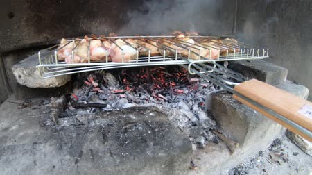 fürj : Making chicken grill barbecue over wood fire in stone fireplace during picnic Stock mozgókép