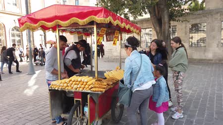 kukoricacső : Istanbul, Turkey - December 2018: A street cart selling boiled corns in the busy district of Eminonu Stock mozgókép