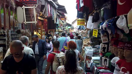 安価な : Istanbul, Turkey - October 2019: People walking and shopping in narrow bazaar roads of Eminonu district, the old city of istanbul near spice bazaar 動画素材
