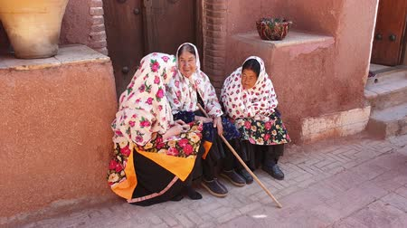 isfahan : Abyaneh, Iran - May 2019: Elder women with traditional Persian clothes chatting in an old street