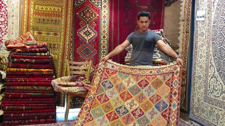szövetek : Isfahan, Iran - May 2019: Young Iranian carpet seller presenting Persian carpets to tourists in a carpet shop