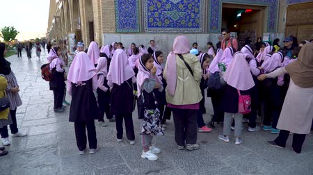 isfahan : Isfahan, Iran - May 2019: Iranian school girls and tourists at entrance to Sheikh Lotfollah Mosque in Isfahan Naqsh-e Jahan Square Stock Footage