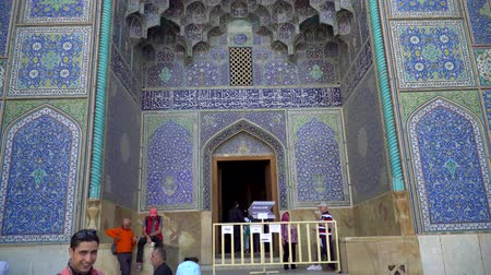 イラン : Isfahan, Iran - May 2019: Tourists and local people at entrance to Sheikh Lotfollah Mosque with tiles on walls in Isfahan Naqsh-e Jahan Square 動画素材