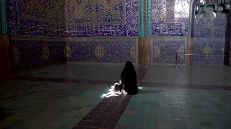 esfahan : Isfahan, Iran - May 2019: Unidentified Iranian woman wearing chador praying inside Sheikh Lotfollah Mosque with tiles on walls, Isfahan, Iran Stock Footage