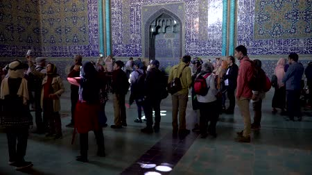 esfahan : Isfahan, Iran - May 2019: Tourists inside Sheikh Lotfollah Mosque examining and taking photos of tiles on walls Stock Footage