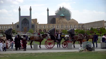 isfahan : Isfahan, Iran - May 2019: Horse carriages waiting for tourists and Iranian people to have a ride around Isfahan Naqsh-e Jahan Square also called Imam Square Stock Footage