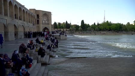 persie : Isfahan, Iran - May 2019: Khaju bridge over Zayandeh river with tourists and local people walking around