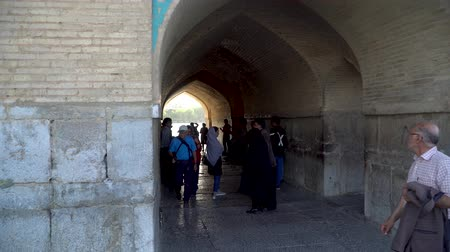 esfahan : Isfahan, Iran - May 2019: Khaju bridge over Zayandeh river with tourists and local people walking around