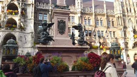 bajor : Munich, Germany - October 2019: The statue in Munich Marienplatz square with Marientplatz Town hall, Munchen city centre old town Stock mozgókép