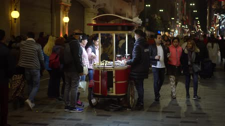 castanha : Istanbul, Turkey - November 2019: Man selling roasted chestnut with crowd people street walking in Istanbul city life