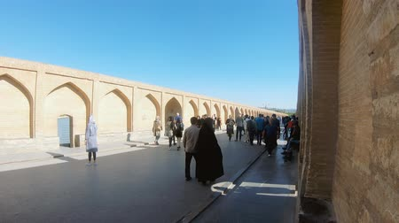 isfahan : Isfahan, Iran - May 2019: Khaju bridge over Zayandeh river with tourists and local people walking around