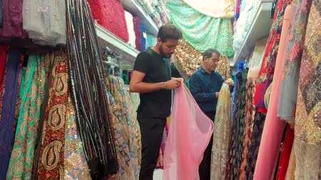 isfahan : Isfahan, Iran - May 2019: Men selling textiles and clothing in Bazar Bozorg, also known as the Grand Bazaar Stock Footage