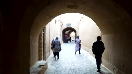 estreito : Yazd, Iran - May 2019: Iranian people walking in the traditional narrow alley with arches in the old town of Yazd, Iran Stock Footage