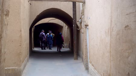минарет : Yazd, Iran - May 2019: Iranian people walking in the traditional narrow alley with arches in the old town of Yazd, Iran Стоковые видеозаписи