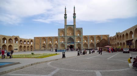 persie : Yazd, Iran - May 2019: Entrance gate and minarets of Jameh Mosque of Yazd, with iranian people and tourists walking Dostupné videozáznamy