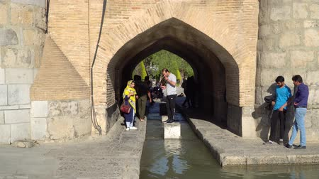 isfahan : Isfahan, Iran - May 2019: Iranian people walking under SioSePol or Bridge of 33 arches, one of the oldest bridges of Esfahan