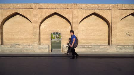 isfahan : Isfahan, Iran - May 2019: Iranian people walking over SioSePol or Bridge of 33 arches, one of the oldest bridges of Esfahan