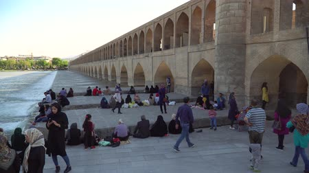 anão : Isfahan, Iran - May 2019: Iranian people relaxing around SioSePol or Bridge of 33 arches, one of the oldest bridges of Esfahan