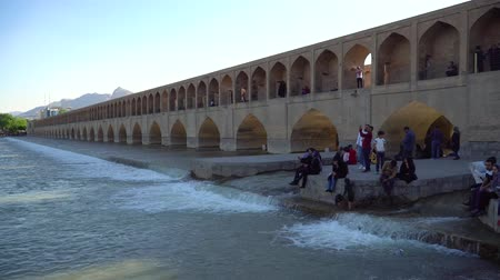 isfahan : Isfahan, Iran - May 2019: Iranian people relaxing around SioSePol or Bridge of 33 arches, one of the oldest bridges of Esfahan