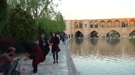 khan : Isfahan, Iran - May 2019: Iranian people walking over SioSePol or Bridge of 33 arches, one of the oldest bridges of Esfahan