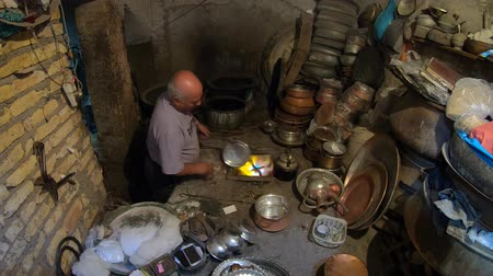 isfahan : Yazd, Iran - May 2019: Iranian man working with copper cookware in his copper store Stock Footage