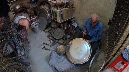isfahan : Yazd, Iran - May 2019: Old Iranian man working with his hammer in a store with various old tools Stock Footage