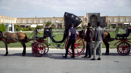 Isfahan, Iran - May 2019: Horse carriages waiting for tourists and Iranian people to have a ride around Isfahan Naqsh-e Jahan Square also called Imam Square Stock Footage
