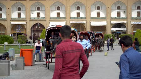 Isfahan, Iran - May 2019: Horse carriages waiting for tourists and Iranian people to have a ride around Isfahan Naqsh-e Jahan Square also called Imam Square Стоковые видеозаписи