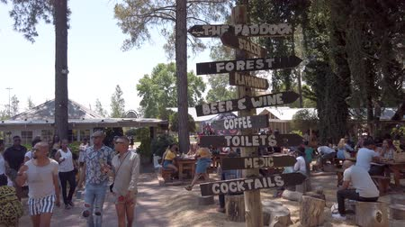 midye : Johannesburg, South Africa - October 2019: Directional signage in Fourways Farmers Market with people eating and socializing