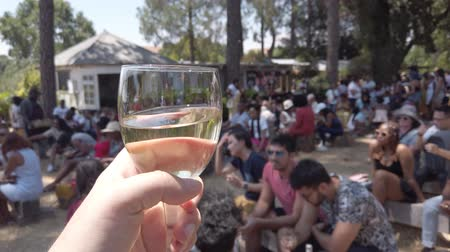 Johannesburg, South Africa - October 2019: Hand holding a glass of white wine in Fourways Farmers Market with people eating and socializing