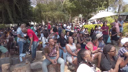 Johannesburg, South Africa - October 2019: South African people listening to a musician on stage while eating and socializing at Fourways Farmers Market