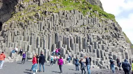 Vik, Iceland - August 2019: Unidentified tourists visiting black sand beach of Reynisfjara, mount Reynisfjall and the volcanic basalt columns in the southern coast of Iceland.