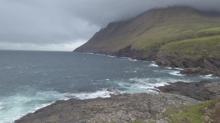 danimarka : Dramatic landscape scenery on Faroe Islands with waves hitting the cliffs and a mountain under fog. The nature of the Faroe Islands in the north Atlantic Stok Video