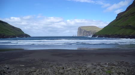 danimarka : Risin and Kellingin rocks as seen from Tjornuvik bay with waves hitting the shore on Streymoy on the Faroe Islands, Denmark, Europe Stok Video