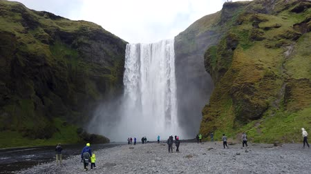 Skogar, Iceland - August 2019: Huge waterfall of Skogafoss with tourists visiting, Skogar, south of Iceland
