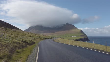 danimarka : Dramatic landscape on Faroe Islands with a road and mountain under fog. Stok Video