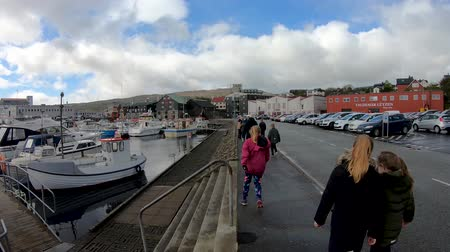 Torshavn, Faroe Islands - August 2019: School kids walking along fishing boats in Torshavn marina harbour on Faroe islands.